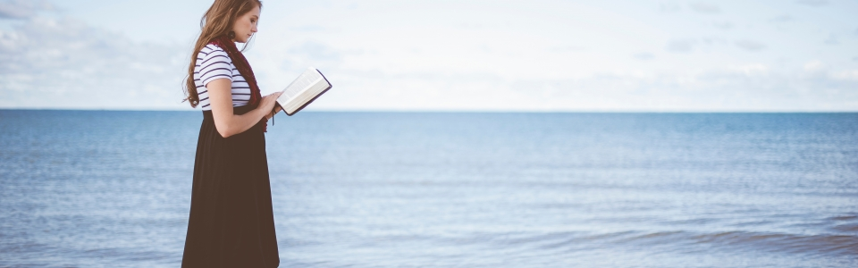 Woman on a beach reading the Bible – 600dpi